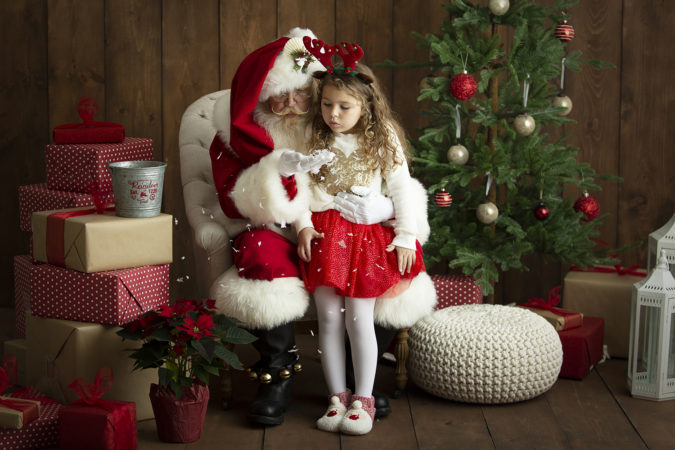 Santa with little girl blowing gold glitter