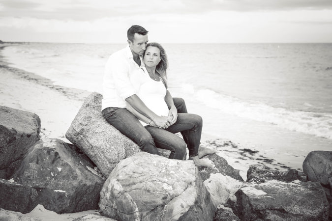 black and white maternity image of couple on jetty at ocean