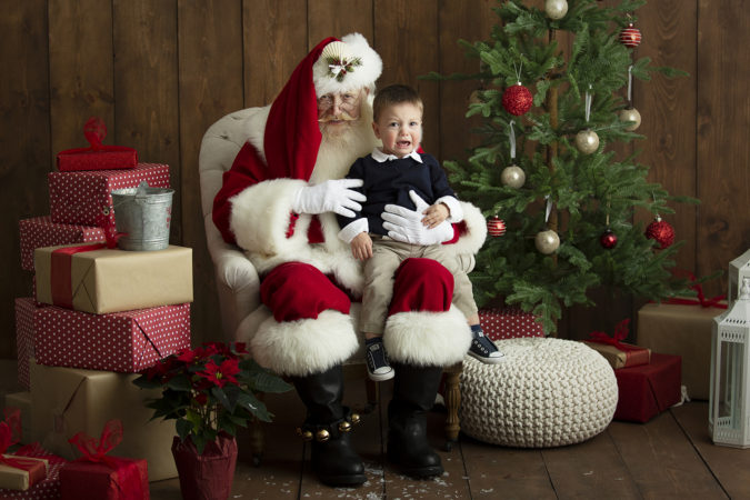 Santa sitting with crying little boy