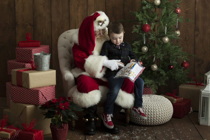 Santa sitting in chair with little boy reading his list