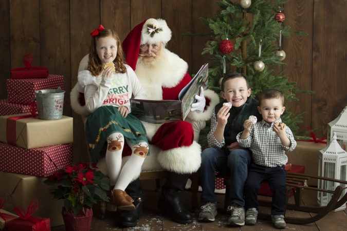 Santa sitting with three children reading book and eating cookies