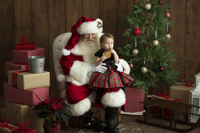 Santa sitting with little girl eating cookie