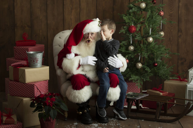 Santa sitting in chair with little boy whispering in ear