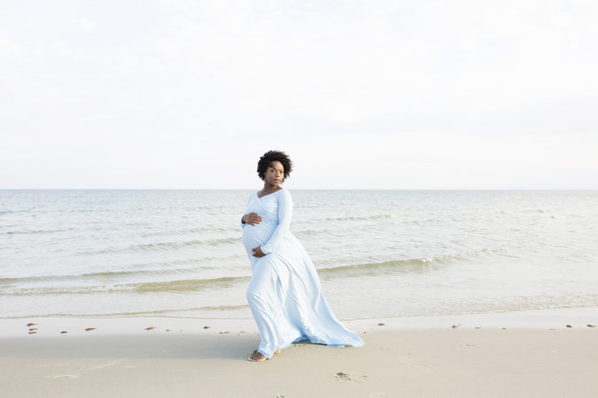 maternity session at beach low tide mother in light blue gown