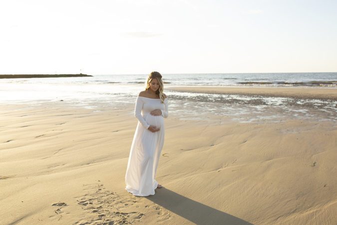 pregnant mother in white gown at beach low tide