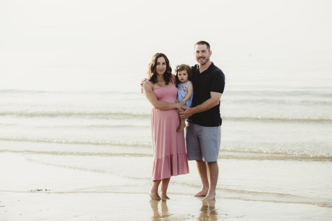 family maternity session at beach low tide parents holding toddler girl