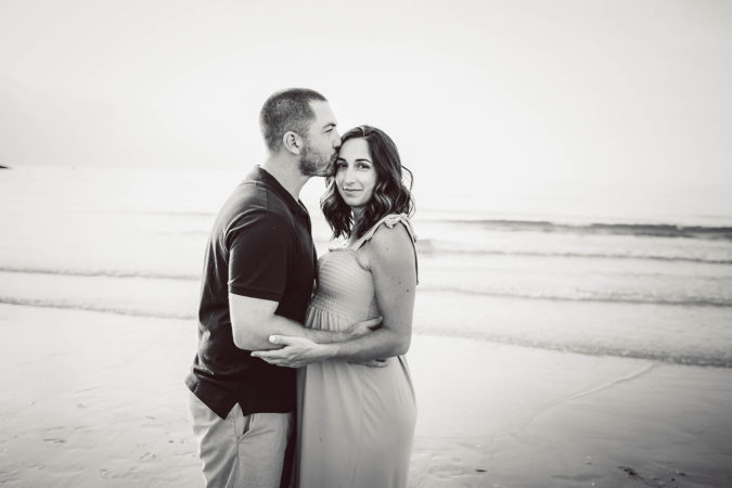 maternity session at beach low tide father kissing mother's head black and white