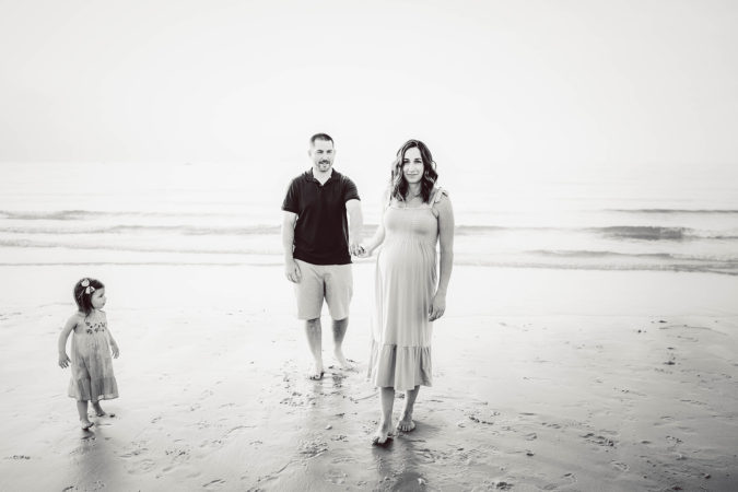 family maternity session at beach low tide parents holding hand toddler girl black and white