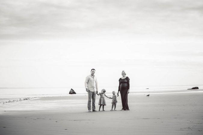 family maternity session parents holding hands with toddlers at beach black and white