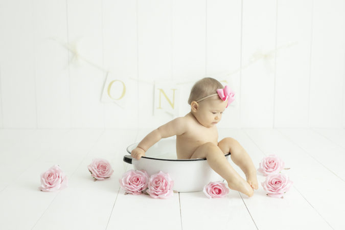 first birthday milk bath little girl pink bow pink flowers feet out of tub