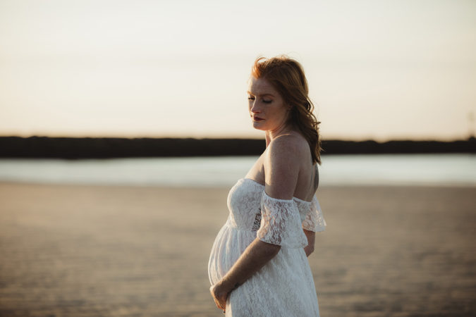outdoor maternity session beach white dress women with red hair